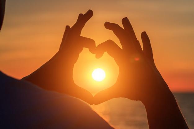 De handen van mannen in de vorm van hart tegen zonlicht in zonsonderganghemel