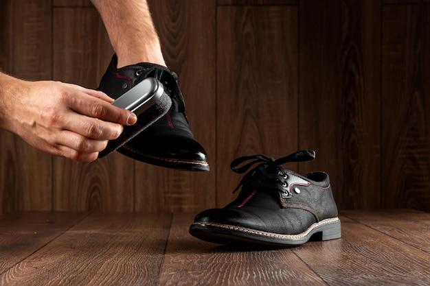 De handen van mannen maken zwarte schoenen op een houten muur schoon. het concept van schoenpoetsen, kledingverzorging, diensten.