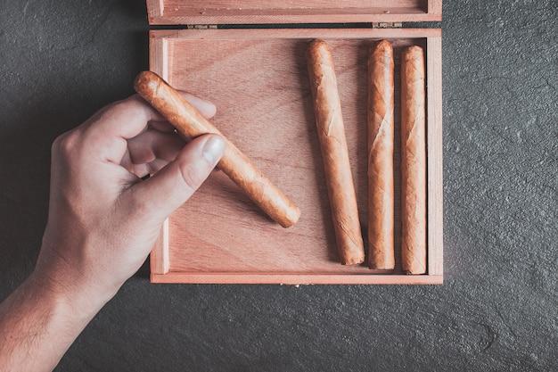 De handen van mannen pakken een sigaar uit de doos op een donkere tafel