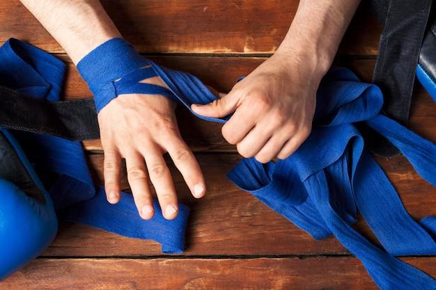 De handen van mannen tijdens het tapen voor een bokswedstrijd tegen een houten oppervlak. het concept van training voor bokstraining of vechten. plat lag, bovenaanzicht