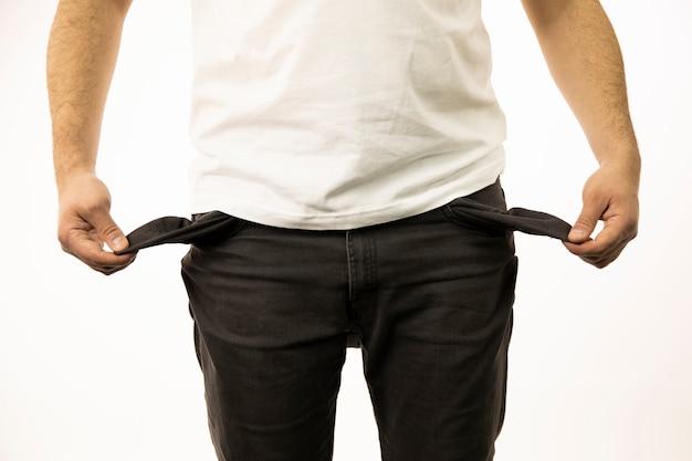 De handen van mannen vertonen lege broekzakken binnenstebuiten