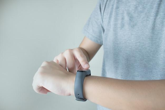 De handen van mensen die grijze t-shirts dragen, gebruiken intelligente horloges om de hartslag te volgen.