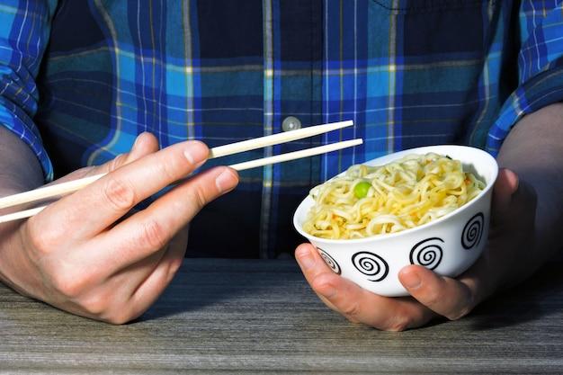 De handen van mensen houden noedels met eetstokjes. chinese noedels, stokken, handen.