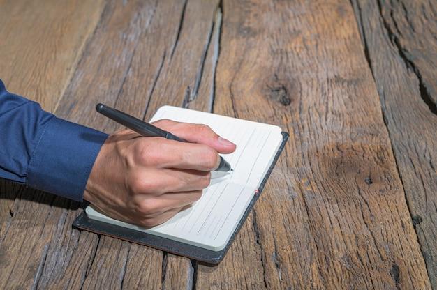 De handen van mensen maken aantekeningen in notitieboekjes