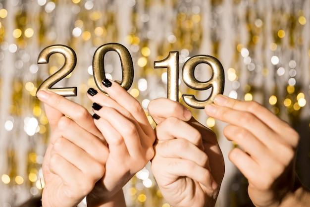 De handen van mensen met 2019-nummers