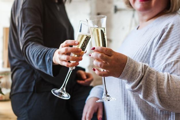 De handen van mensen met glazen champagne, het vieren van een vakantie, groet, vakantie en verjaardag