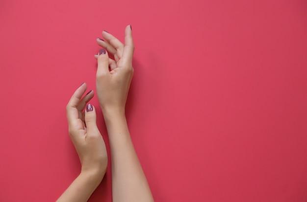 De handen van modieuze in vrouw op rode achtergrond