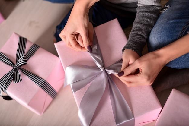 De handen van moeder en dochter die een geschenk uitpakken