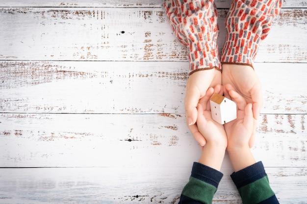 De handen van moeder en kind houden voorzichtig een mooi wit houten speelgoedhuis vast en tonen het gevoel van liefde voor de familie en bescherming. woningkrediet, verzekering, investeringen in onroerend goed, beveiliging. kopieer ruimte.
