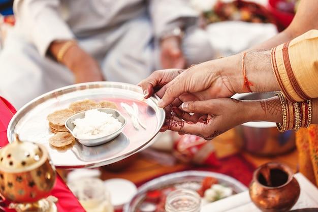 De handen van oude vrouwen houden een plaat met rijst die op indisch huwelijk wordt voorbereid