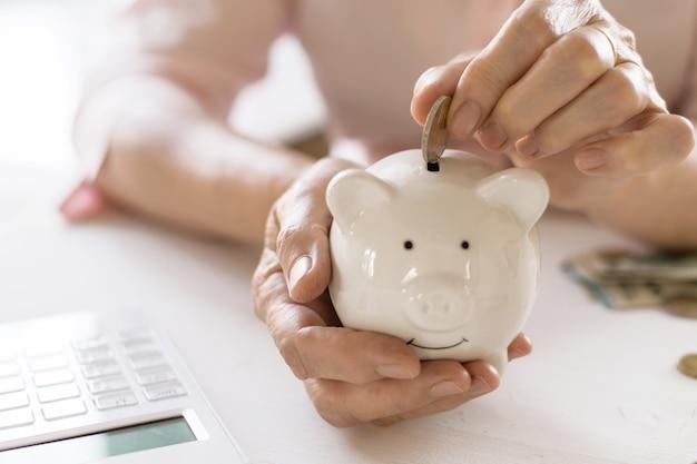 De handen van oude vrouwen zetten geld in het spaarvarken, het concept van pensioen, sparen.