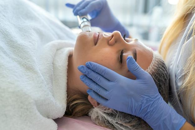 De handen van schoonheidsspecialiste met apparaat voor ultrasoon reinigen vrouw procedure in cosmetologie kliniek doen