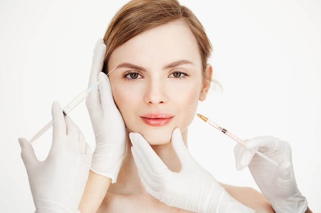 De handen van schoonheidsspecialisten die medische botoxinjecties maken aan mooie blonde. huid optillen. gezichtsbehandeling. schoonheid en spa.