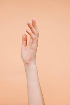 De handen van sideviewvrouw met lichtoranje achtergrond