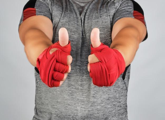 De handen van sportman gewikkeld in rood elastisch sportverband vertonen een soortgelijk teken