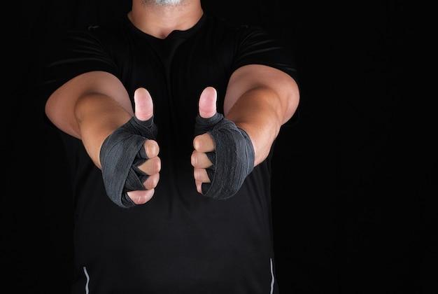 De handen van sportman gewikkeld in zwart elastisch sportverband vertonen een soortgelijk teken