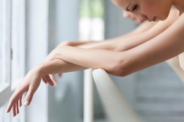 De handen van twee klassieke balletdansers in barre