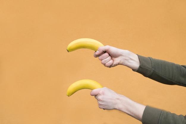 De handen van twee mensen houden twee bananen tegen op een oranje muur