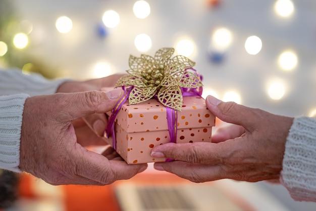 De handen van twee mensen wisselen een kerstcadeau uit geluk en liefde vrolijk kerstfeest gelukkig nieuwjaar