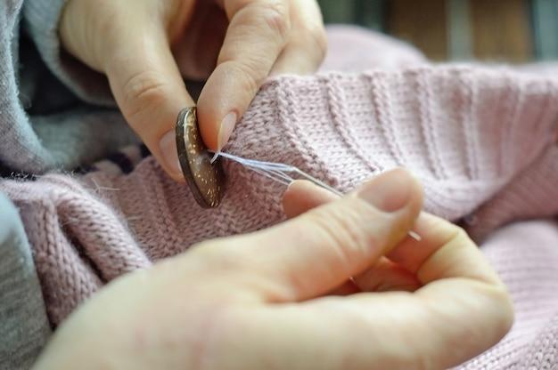 De handen van vrouwelijke arbeiders naaien een houten knoop aan een jas. detailopname.