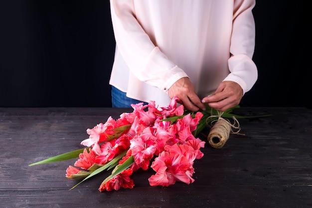 De handen van vrouwen creëren een boeket bloemen van gladiolen