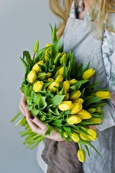 De handen van vrouwen die een armvol gele tulpen houden.