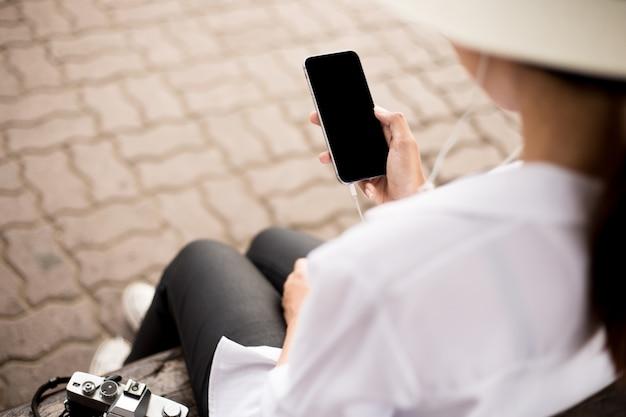 De handen van vrouwen die mobiele telefoons houden