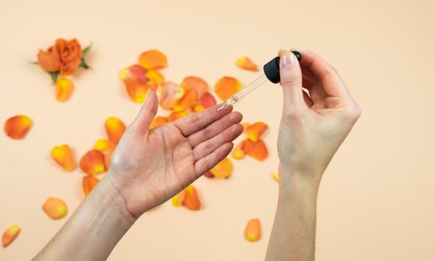 De handen van vrouwen die rozenolie met een druppel toepassen. huidverzorging concept. natuurlijk medicijn.