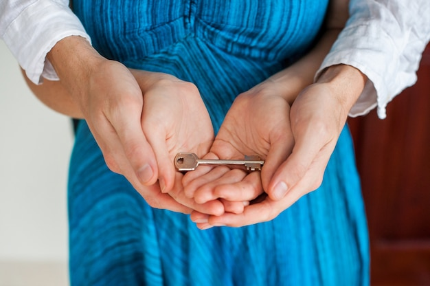 De handen van vrouwen en mannen houden huissleutel in de vorm van hart op de achtergrond een houten deur. het bezit van onroerend goed concept