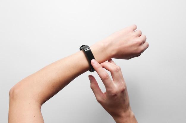 De handen van vrouwen gebruiken slim horloge op grijze lijst. moderne gadgets, bovenaanzicht