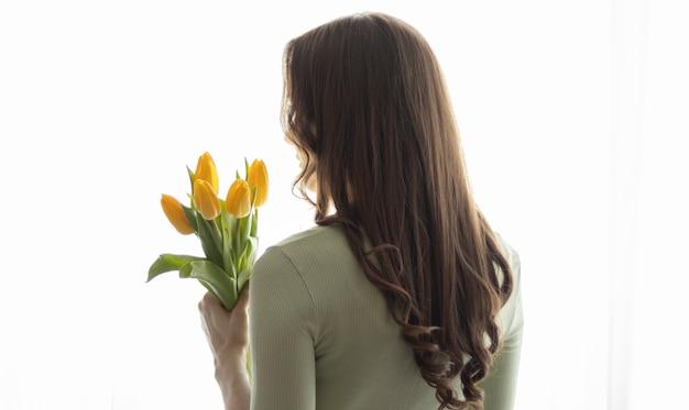 De handen van vrouwen houden een boeket tulpen vast