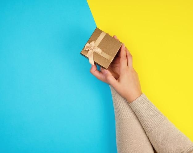 De handen van vrouwen houden een gesloten doos met een boog op een blauw-gele achtergrond