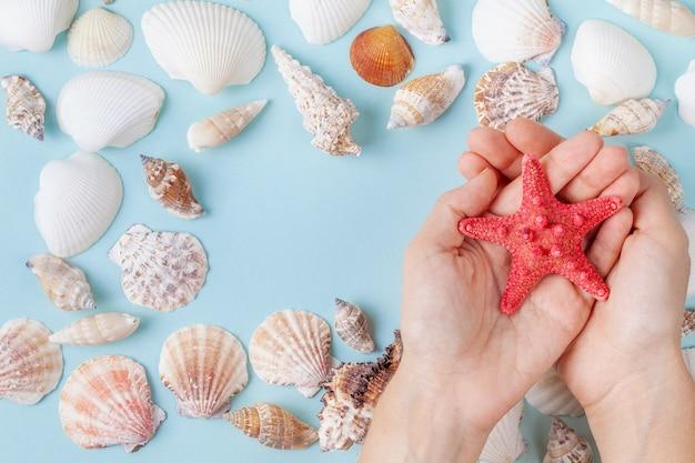 De handen van vrouwen houden een zeester op een blauwe de zomerachtergrond met verschillende shells en zeester