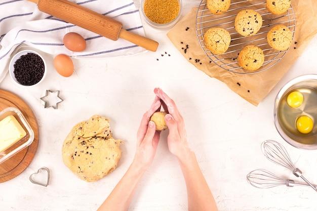 De handen van vrouwen houden het deeg voor het maken van koekjes. culinaire apparatuur en ingrediënten. eieren, meel, suiker, chocolade, boter, bakvormen. plat leggen.