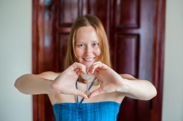 De handen van vrouwen houden huissleutel in de vorm van hart op de achtergrond een houten deur. het bezit van onroerend goed concept
