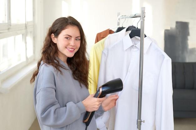 De handen van vrouwen houden stoomboot en wit overhemd vast. proces om kleren thuis te wassen