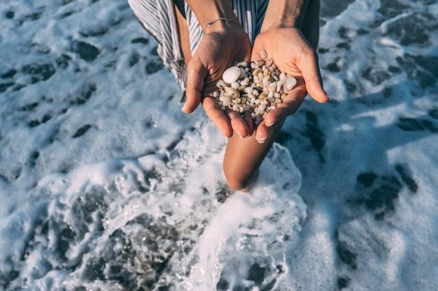 De handen van vrouwen houden veel kleine steentjes vast