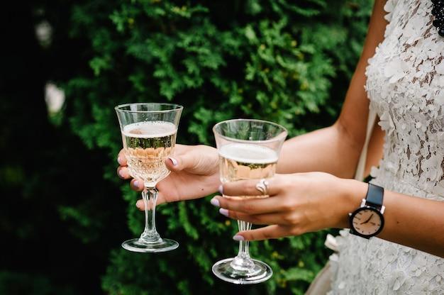 De handen van vrouwen houdt een glas champagne en bruid