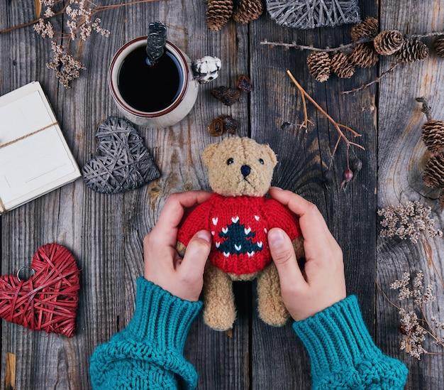 De handen van vrouwen in een groene sweater houden een oude teddy bruine beer