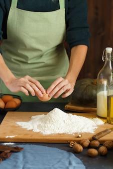 De handen van vrouwen kneden het deeg. de banketbakker duwt een ei in de bloem. op de houten tafel zijn bakken ingrediënten.