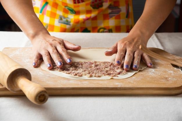 De handen van vrouwen maken azerbeidzjaanse schotel gutab op een houten bord.