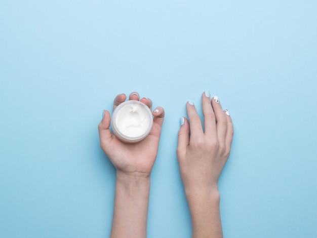 De handen van vrouwen met een potje handcrème op een blauwe ondergrond