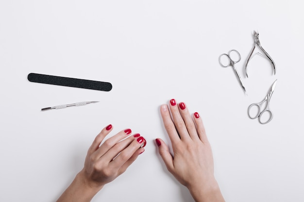 De handen van vrouwen met een rode manicureschaar en een nagelvijl op een witte lijst