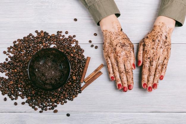 De handen van vrouwen met rode nagellak in een koffiescrub