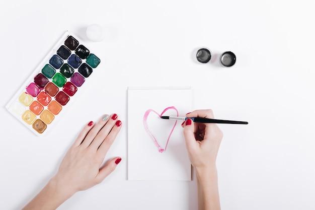 De handen van vrouwen met rood manicure geschilderd waterverfhart in een notitieboekje