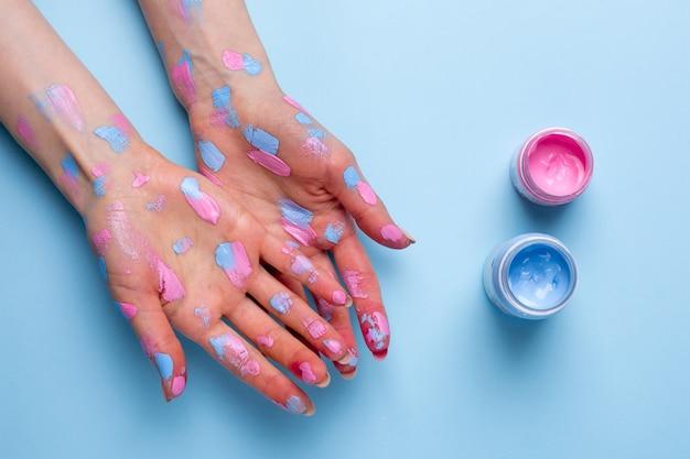 De handen van vrouwen met waterverfpenseelstreken op blauwe oppervlakte