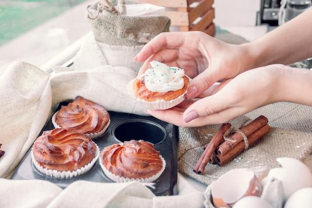 De handen van vrouwen nemen één van cupcake
