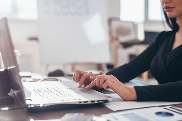 De handen van vrouwen op een laptop toetsenbord in close-up.