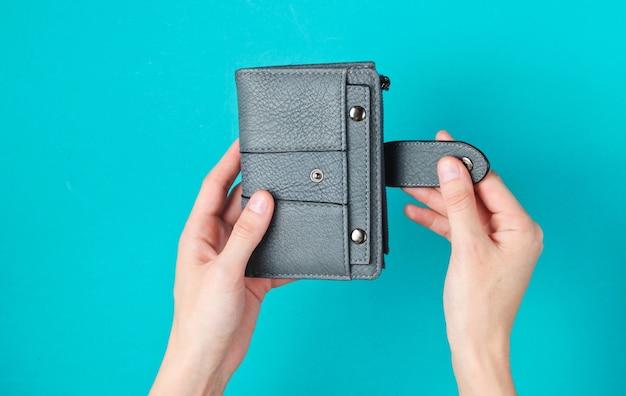 De handen van vrouwen openen leerportefeuille op blauw.