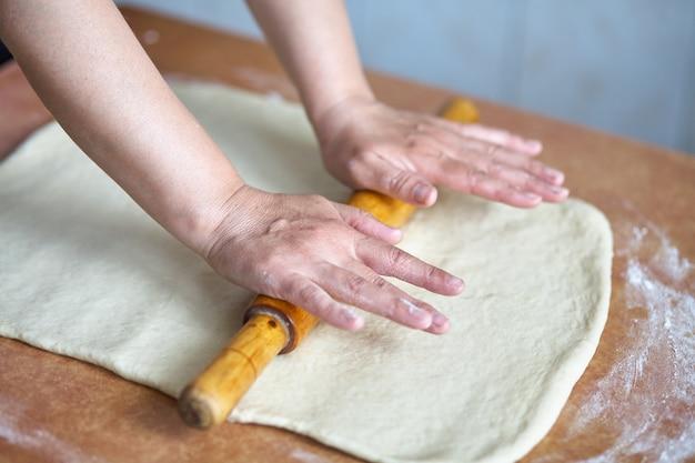 De handen van vrouwen rollen het deeg op de keukentafel. dames handen met deegroller